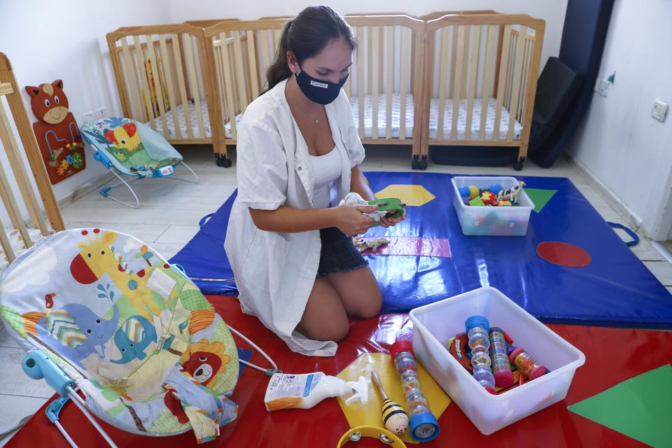 Childcare provider cleaning toys.