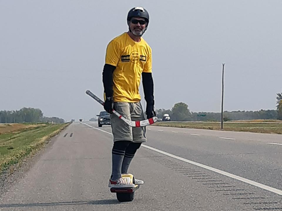 Jonathan Shrier riding a Onewheel on a Canadian Highway