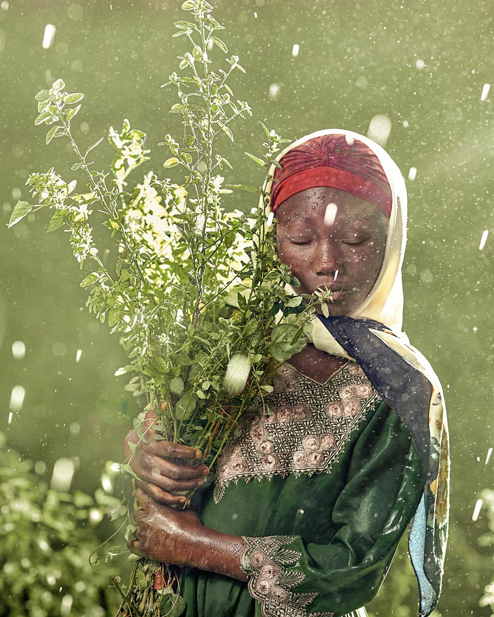 The World We Want, global photo contest: A woman holding a bucket of flowers in the wind.