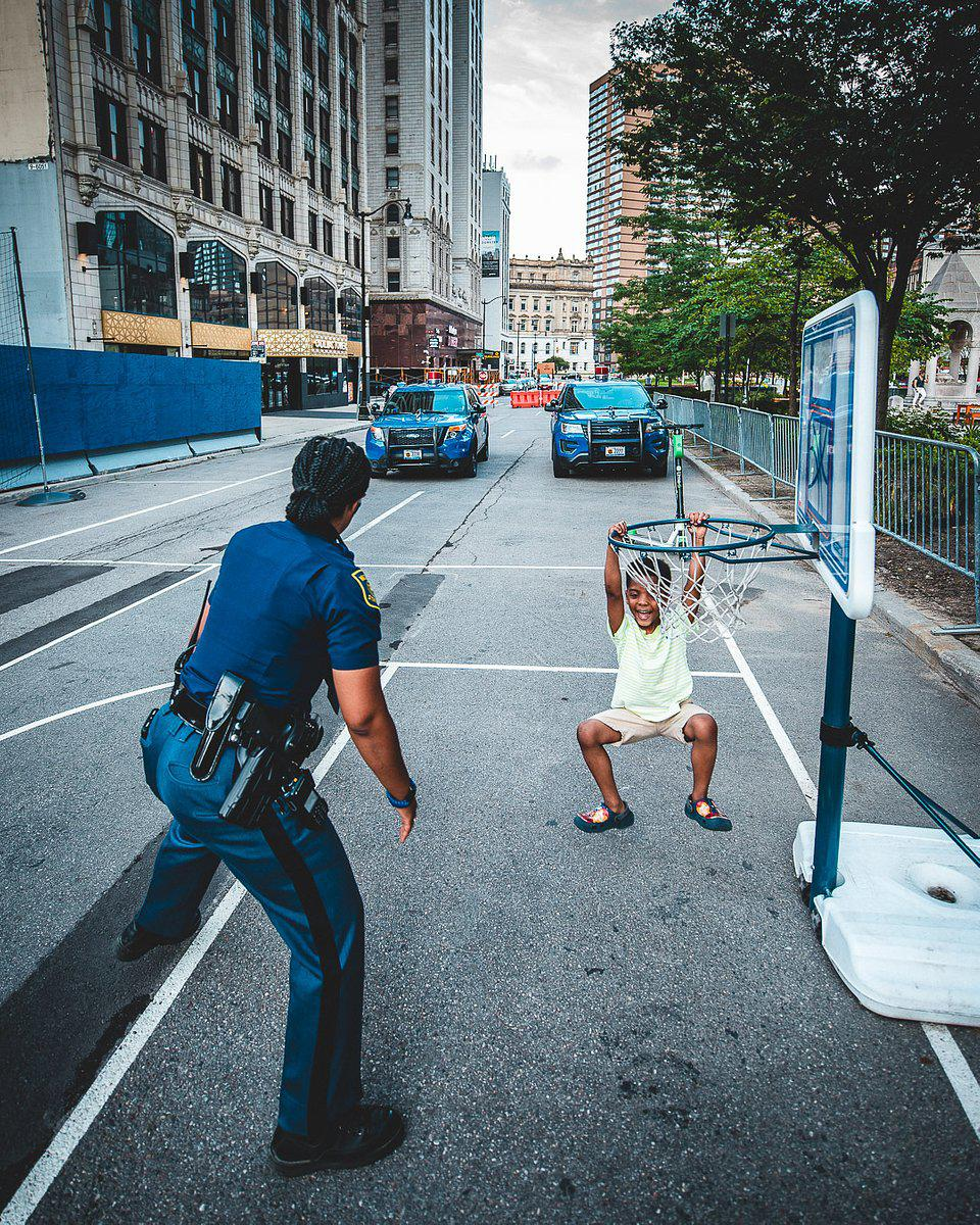 The World We Want, global photo contest; A police woman playing with a boy  in a street of Deltroit