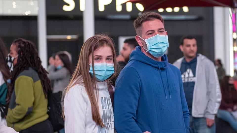 Two people walking down street wearing masks.