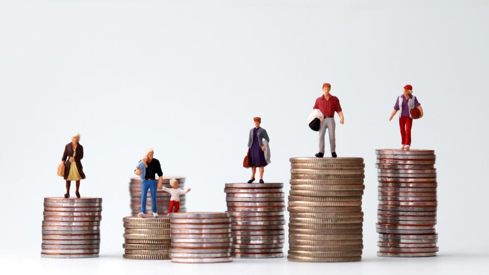 Miniature people standing on piles of different heights of coins. The concepts of person and wealth.