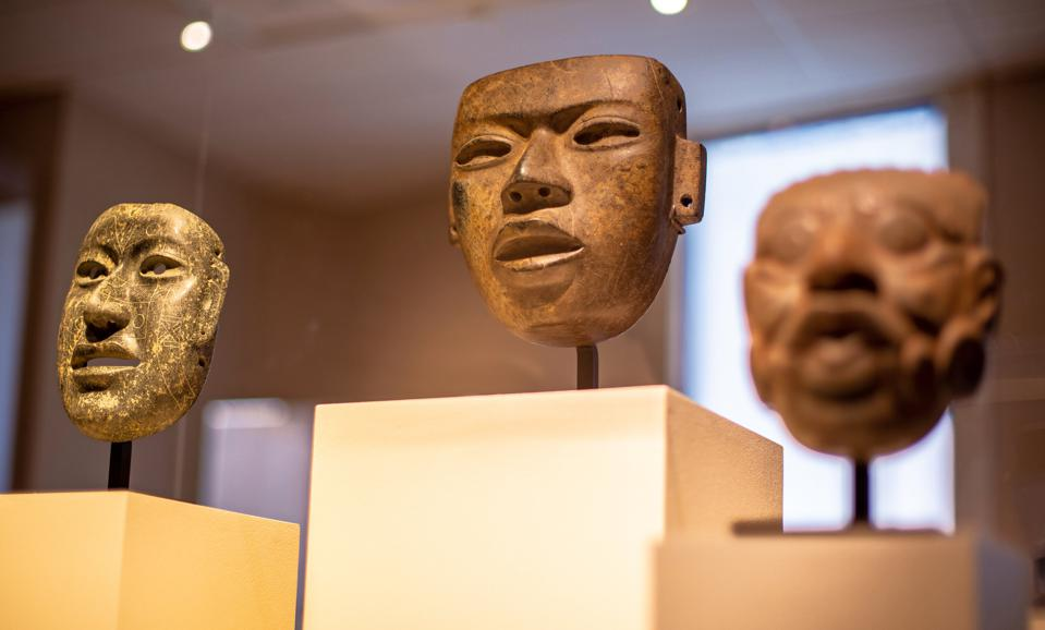 """The MFA, St. Petersburg's Mesoamerican Art gallery, or """"JadeRoom,"""" features jade, serpentine and obsidian, or volcanic glass works (from left to right): Olmec, Mexico, Incised Mask, c. 1,200–400 B.C., Serpentine or Jadeite; Teotihuacán, Mexico, Mask, c. A.D.245–250, Serpentine; and Maya, Guatemala(?), Mask of the Sun God, Kinich Ahau, c.100B.C.–A.D. 350, Jade. All gifts of Dr. Robert L. and Chitranee Drapkin."""