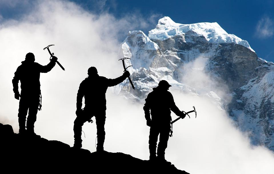 men with ice axe in hand and mountains with clouds