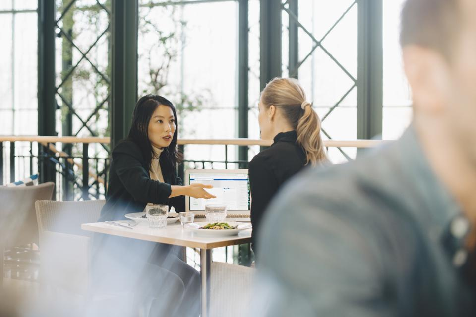Confident businesswomen planning strategy at table during meeting in cafeteria