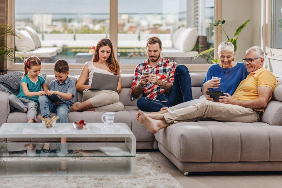 Happy extended family relaxing on the sofa and using wireless technology.