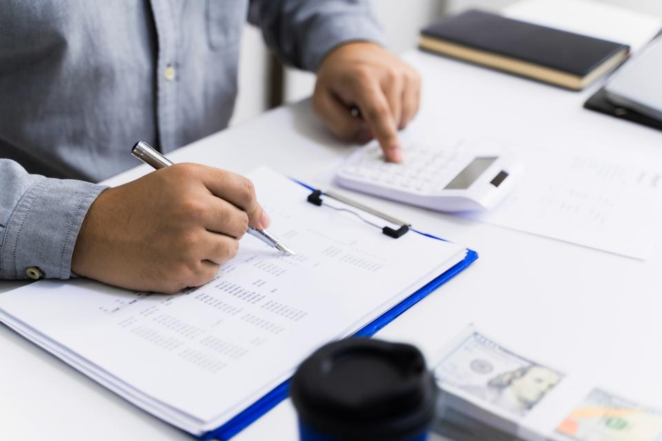 Accountant calculating valuation of financial  data paperwork.