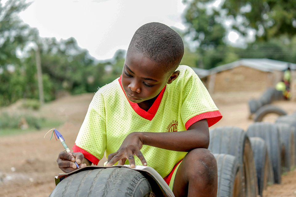 The World We Want, global photo contest: small boy doing homework on a tire.