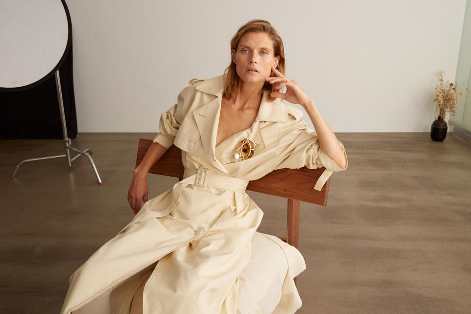 A model sits casually in a photo studio wearing a baggy beige trench coat cinched at the waist.