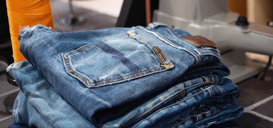 A stack of four pairs of Nudie brand jeans that are clearly used and worn.