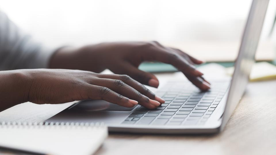 Black woman typing on laptop keyboard while working in office