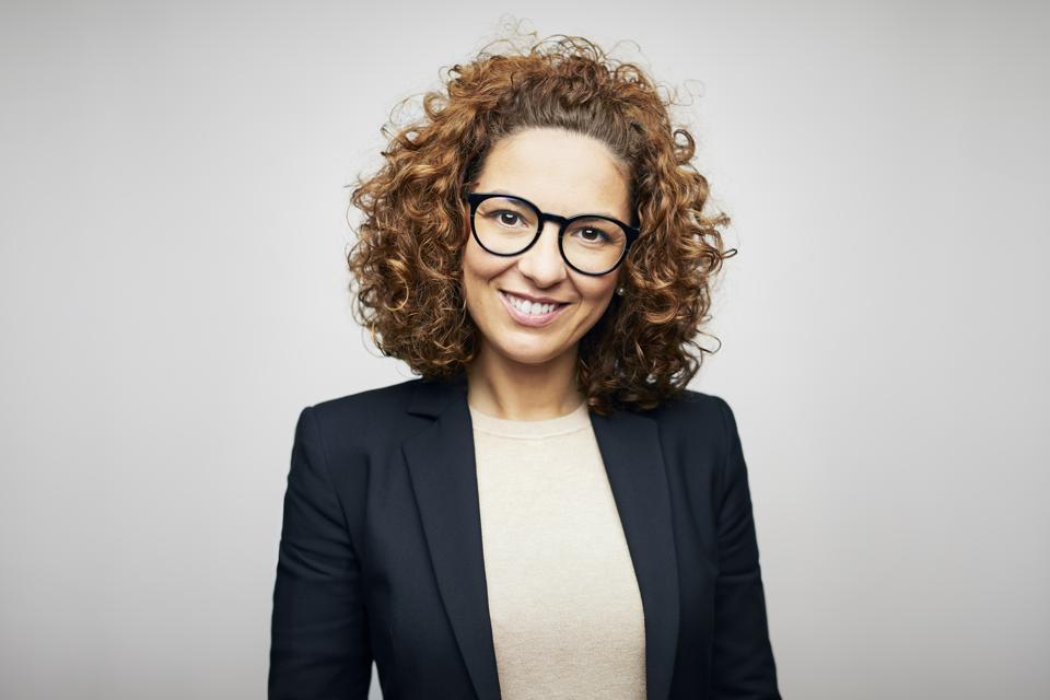 Smiling female brunette CEO wearing eyeglasses and black business jacket.