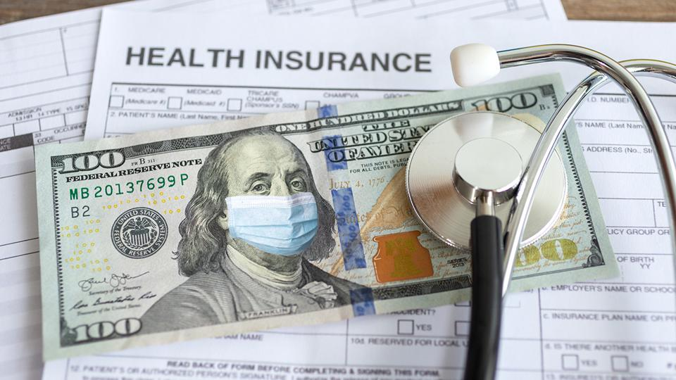 Stack of insurance papers, $100 bill with a masked Ben Franklin and a stethoscope.