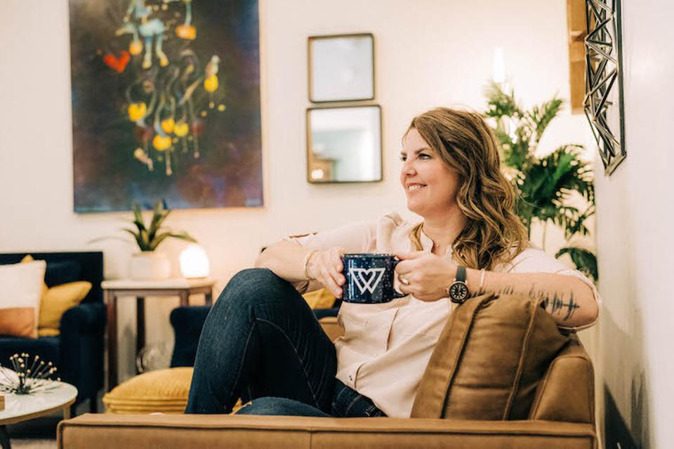 Woman sitting on couch relaxed holding a Wondercide mug