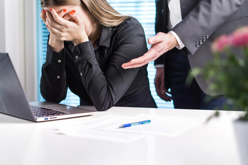 Upset woman crying in office. Getting fired from job. Business man or boss apologizing, comforting or supporting assistant. Businesswoman hurt her feelings or made mistake.