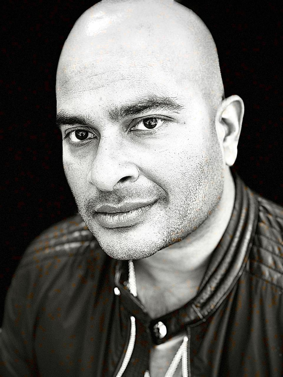 A black and white headshot of a bald man in a dark jacket