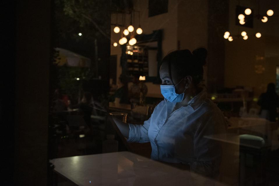Waitress wearing a face mask standing in a dark restaurant