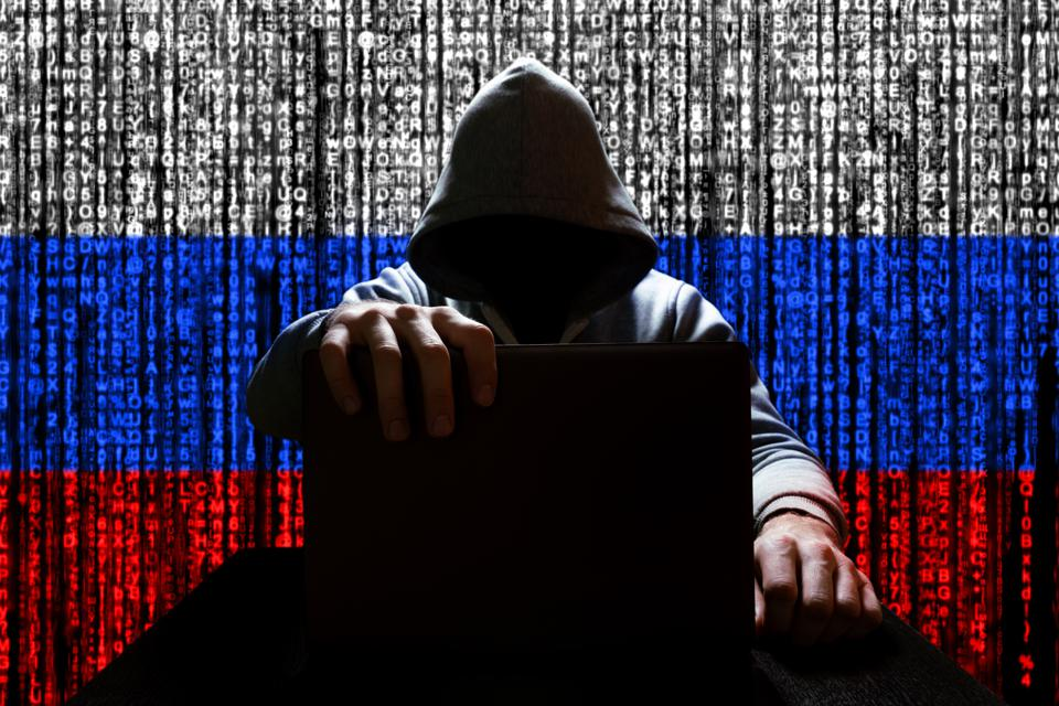 Russian hacker closes the lid of the laptop, against the backdrop of a binary code, the color of the Russian tricolor