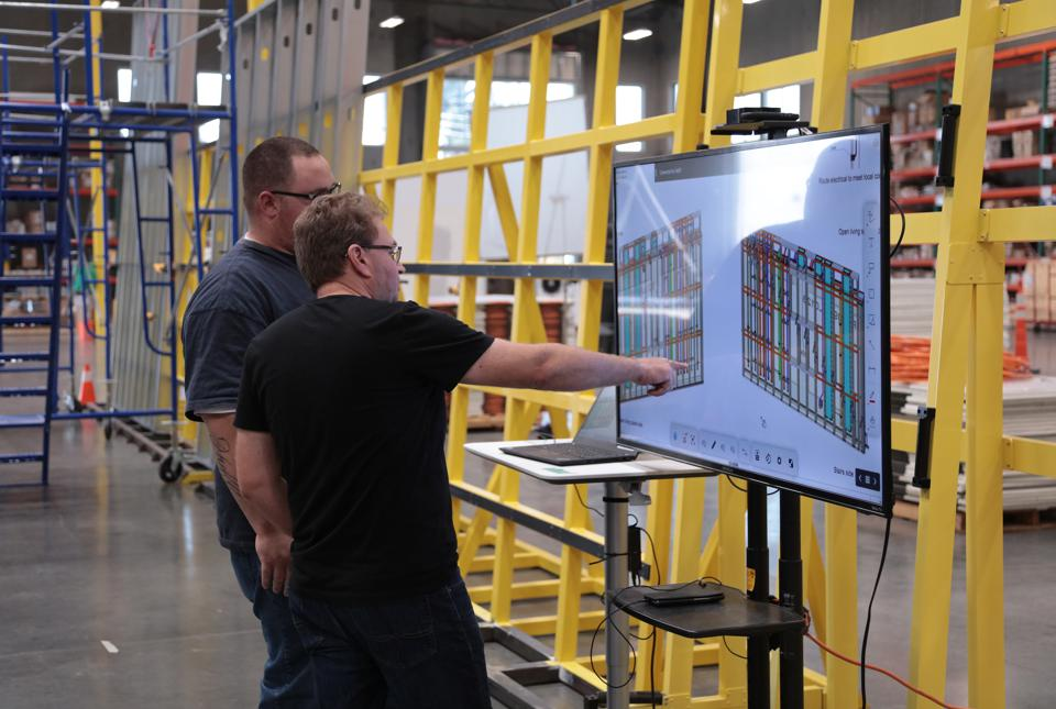 Amit Haller, CEO and co-founder of Veev (front), talks to a team member about building designs, in his factory where walls are being assembled in the background.