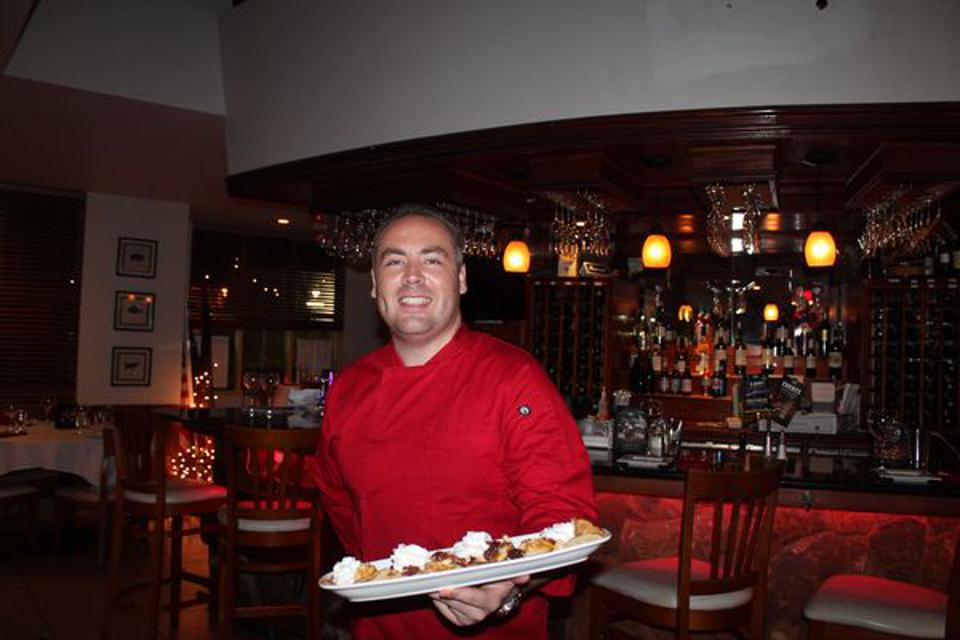 A man in a red shirt holding a plate of food standing next to a restaurant bar