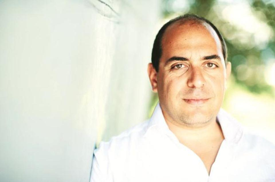 A middle-aged man in a white button-up shirt leaning against a white wall