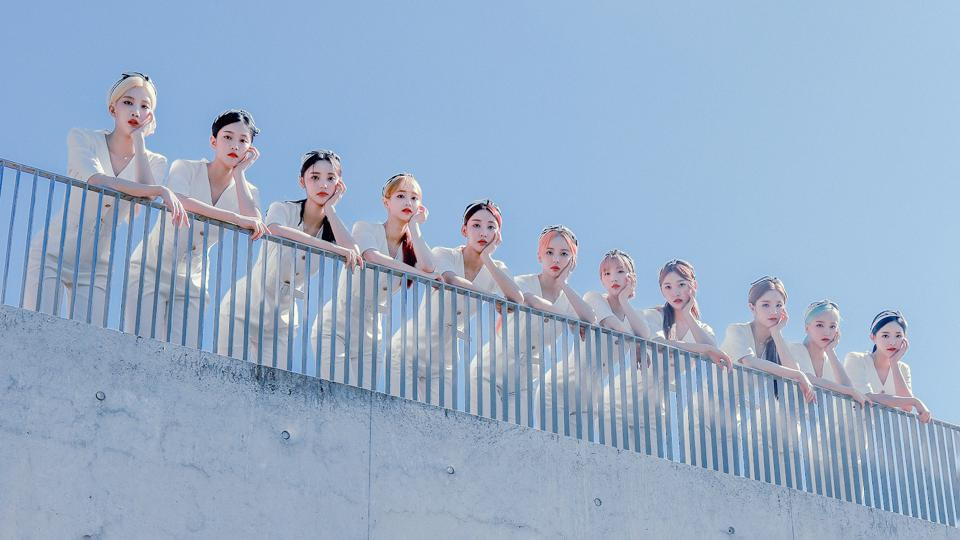 Girl group Loona leaning on a fence, each member with her face resting on her arm.