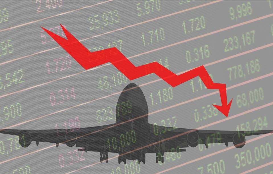 Airplane silhouette in background, stock market chart with curve going down in the foreground.