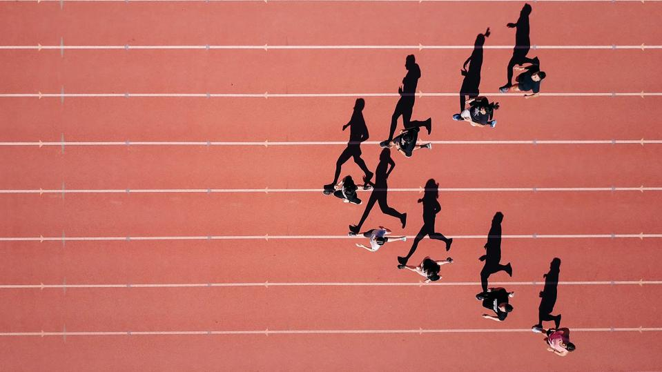 Overview and shadow of men and women running in the form of an arrow on a red track