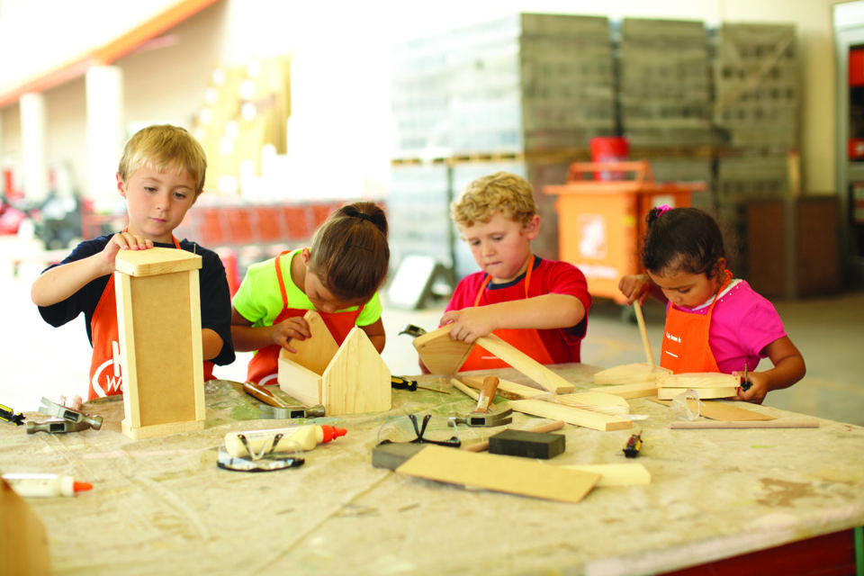 Four children assemble wood pieces from a Home Depot project kit.