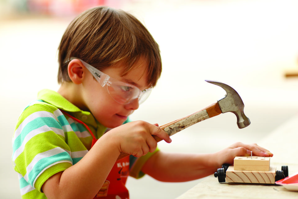 A boy uses a hammer to build a vehicle out of wood.