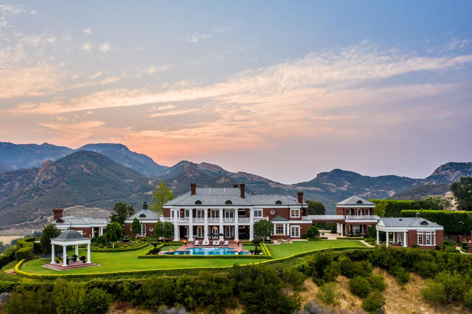 A Colonial Revival-style estate with mountains in the background.