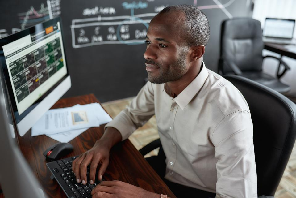 Male trader sitting by desk and studying analytical reports
