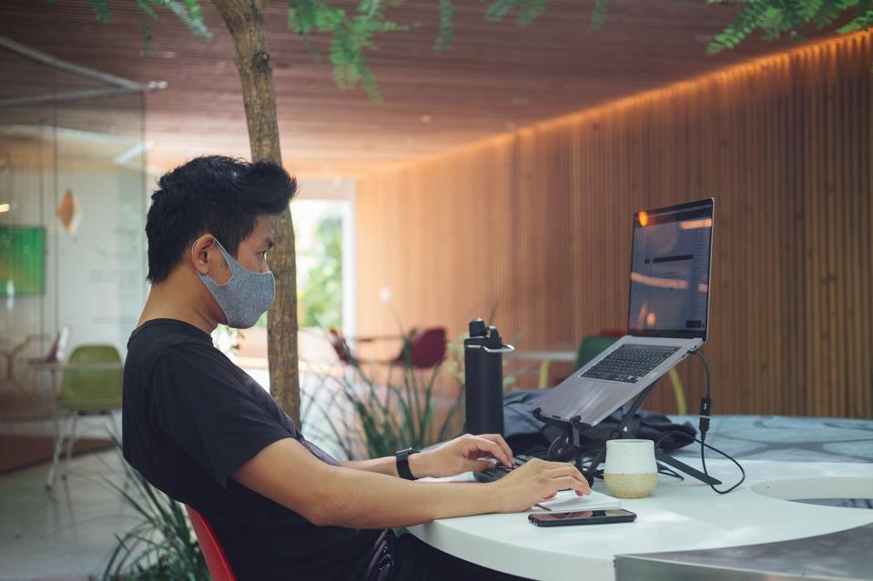 A photo of a man at a desk reading on his laptop with a covid mask.