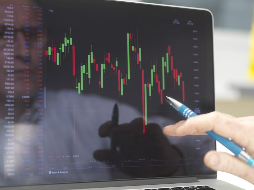 Reflection of a stock trader viewing the performance of a company share price on screen