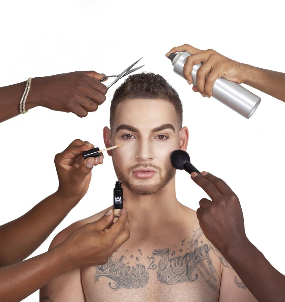 Makeup and hairstylists are making over a man.