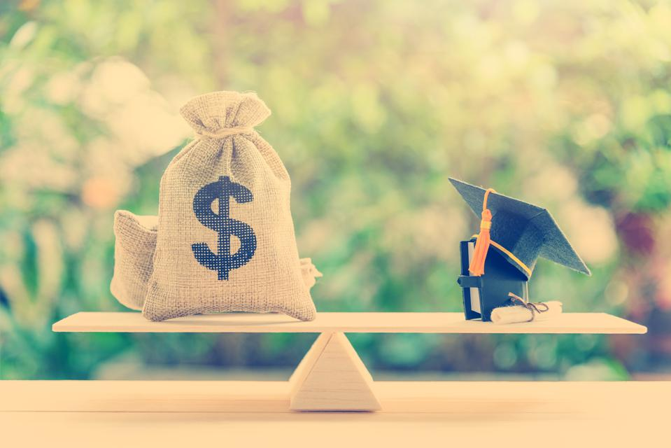 US dollar bills / cash in hessian bags, a black graduation cap or hat, a certificate / diploma and a book on simple balance scale.