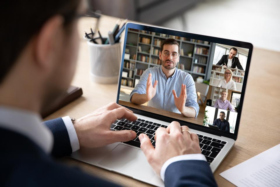 View over businessman shoulder laptop screen and videocall diverse participants