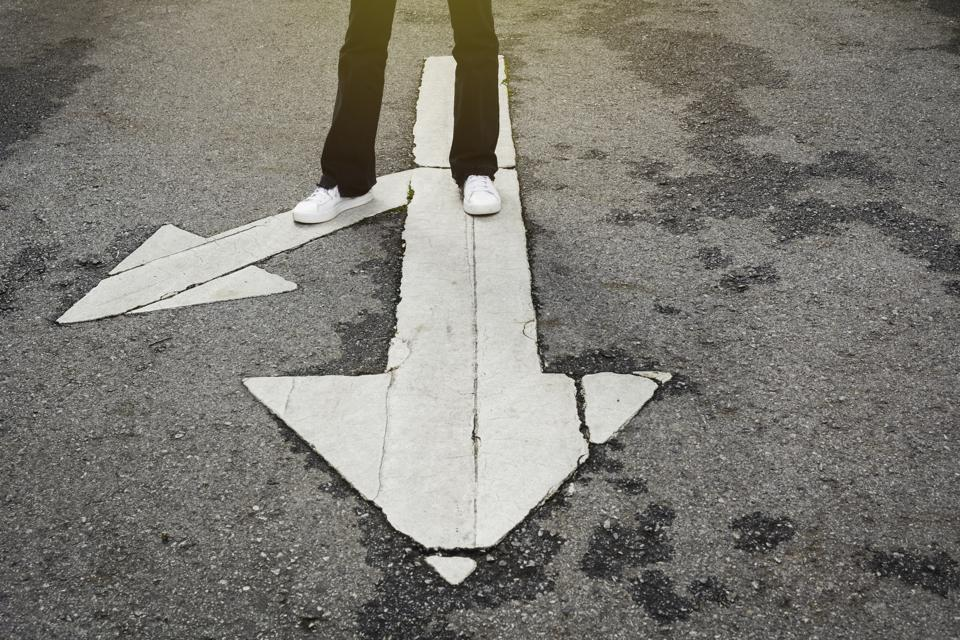 Person standing at a crossroad deciding which way to go