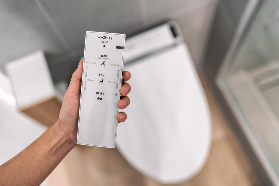 Smart japanese bidet automated toilet washlet with remote for easing cleaning rinsing with water without using toilet paper. at home bathroom modern lifestyle