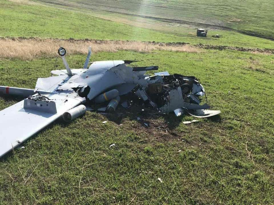 Destroyed TB2 drone sits in green field with MAM-L missiles scattered next to wing.