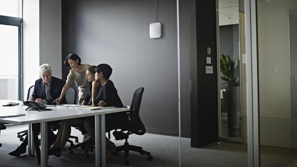 Workers in office with a Netgear WAX 610 wireless access point on the wall.