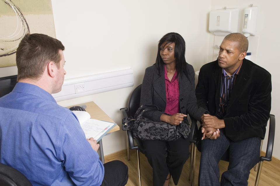 Doctor talking to couple holding hands