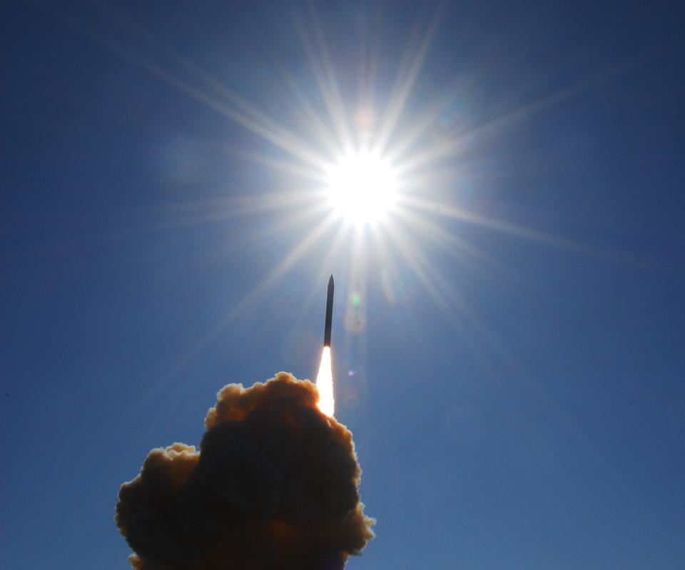 A missile from the GMD system being test-launched into a blue sky.