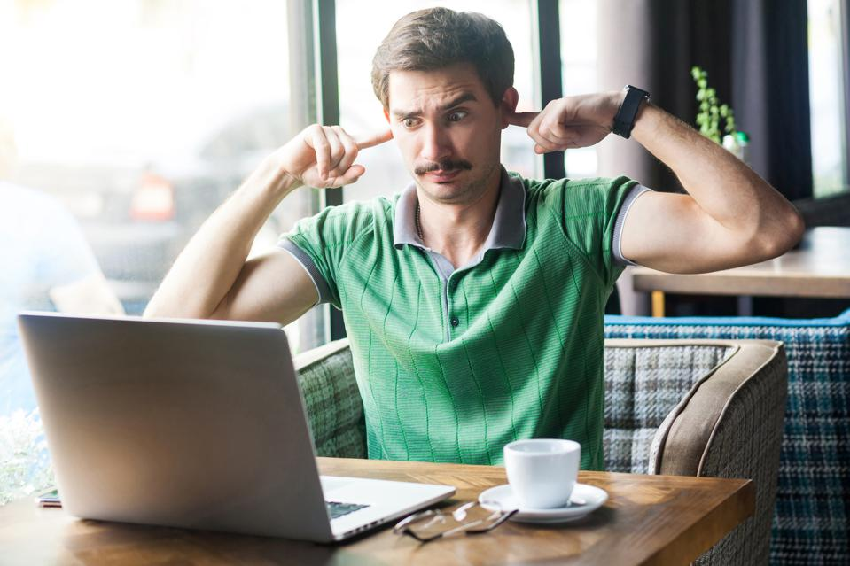I don't want to hear you! Young dissatisfied businessman in green t-shirt sitting, looking at laptop screen on video call and blocking his ears
