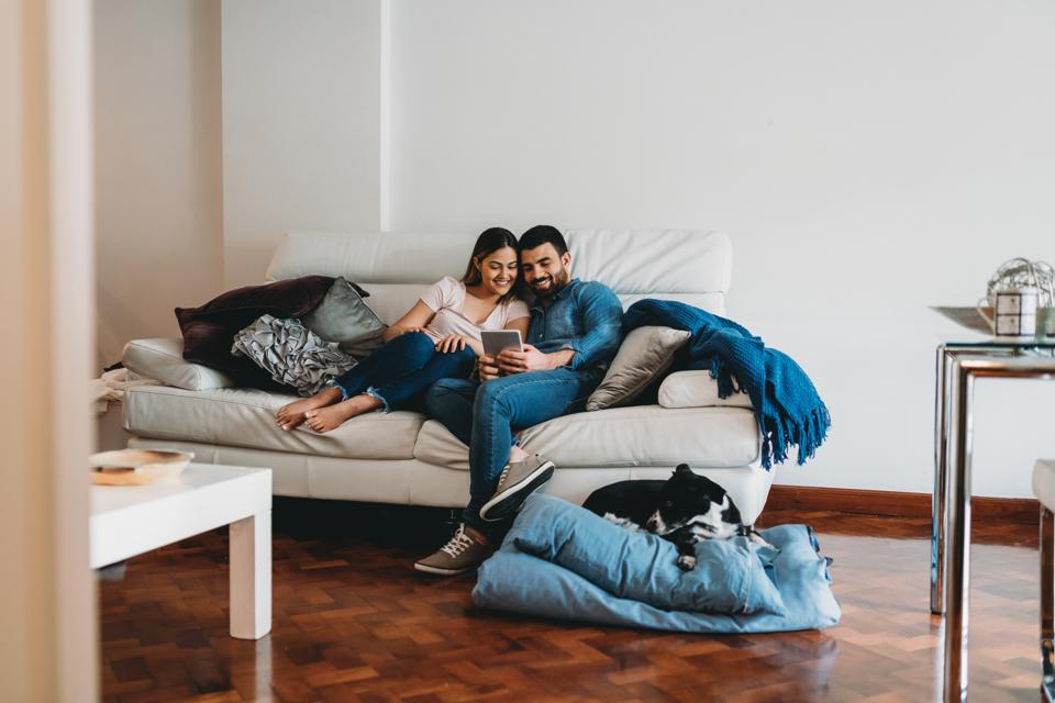Young adult couple together at home. They are sitting on the sofa using a tablet together