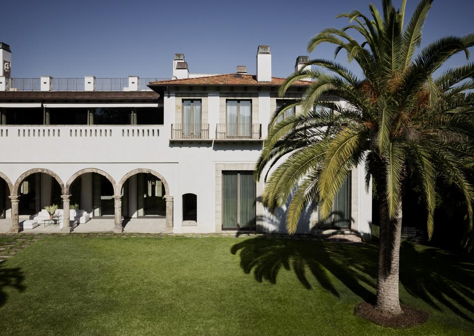 The home has a Spanish Colonial-style exterior overlooking a massive lawn.