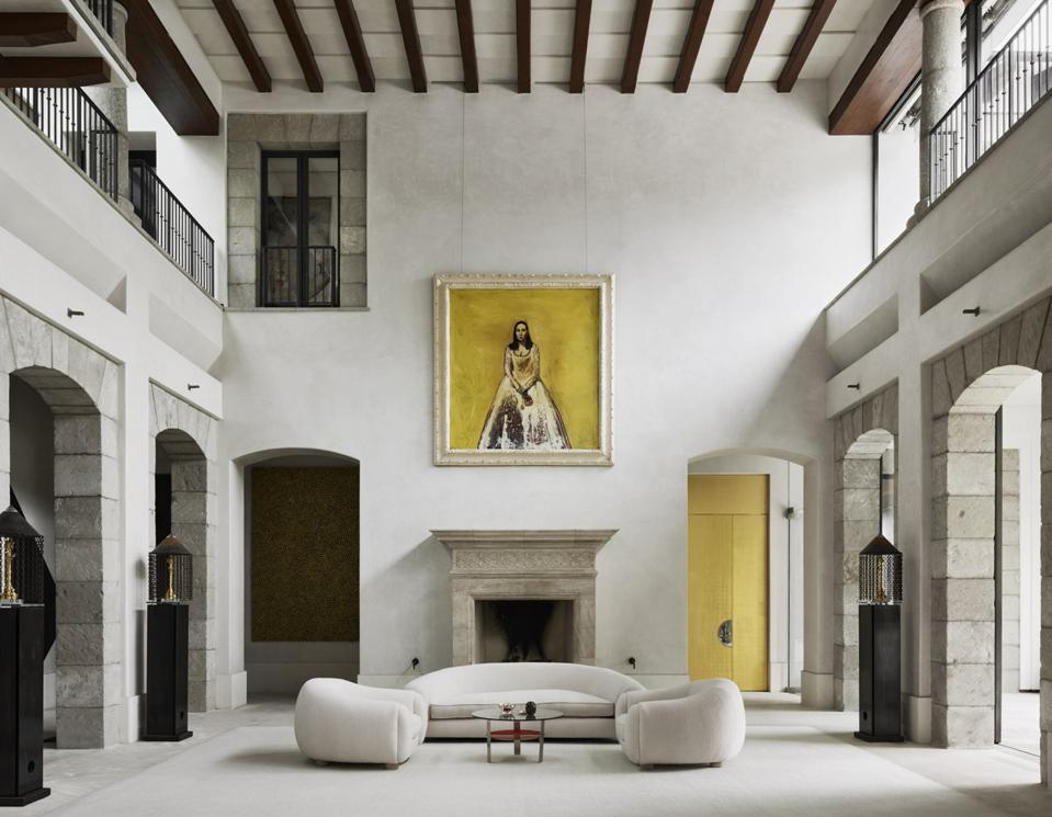 A living room with 30-foot ceilings and a bright pop of contemporary art.