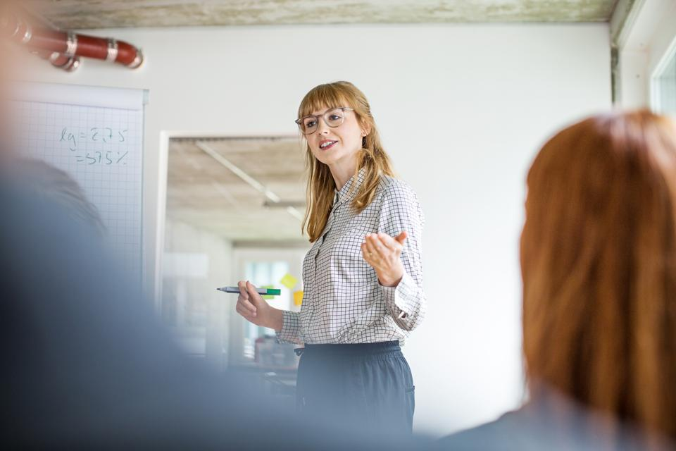 Confident businesswoman giving presentation to colleagues in office