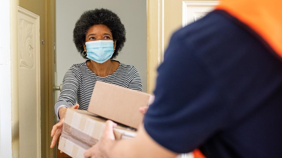 Woman getting package from delivery person during pandemic