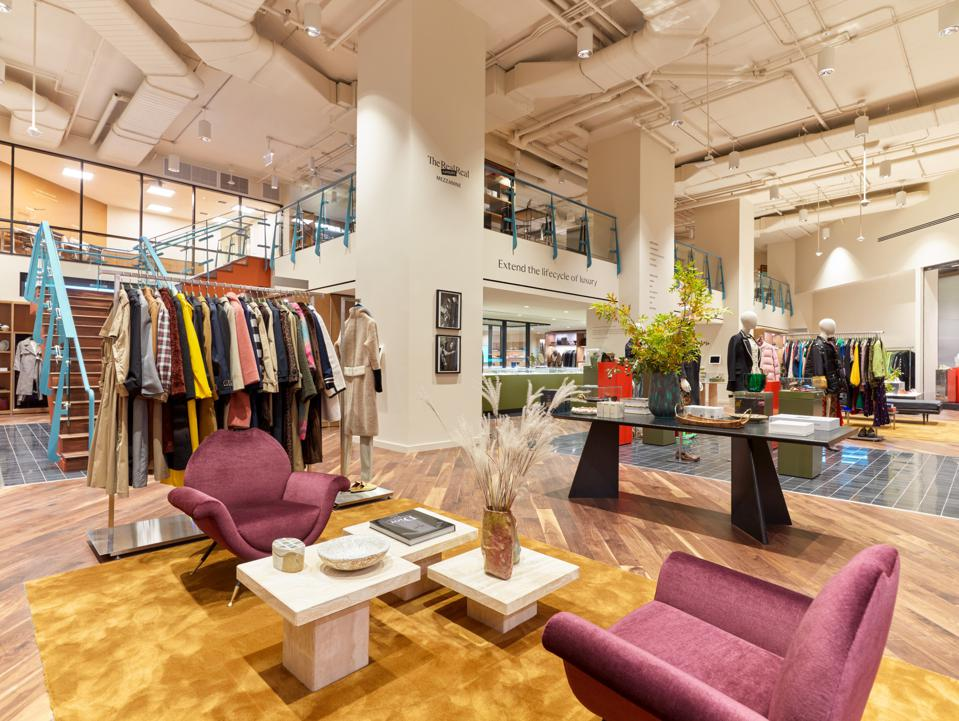 The women's area of The RealReal's Chicago store features exposed ductwork, pink chairs and marble coffee tables.